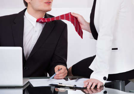 Young businesswoman pulling male colleague's tie while seducing him at desk in office photo