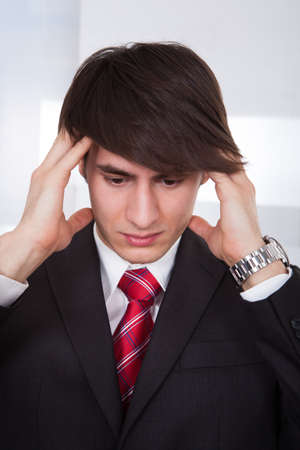 Young businessman suffering from headache while calculating finance at desk in office photo
