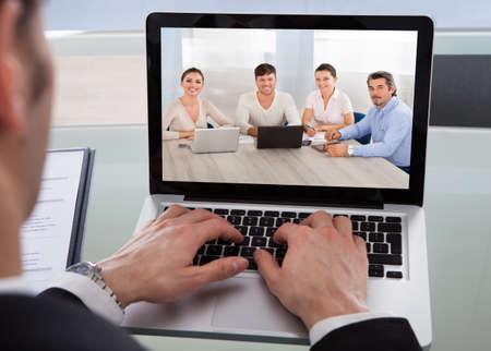 entrevista: Recorta la imagen de hombre de negocios usando la computadora port�til en el escritorio en la oficina Foto de archivo
