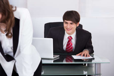 Young businessman staring at woman's back in office photo