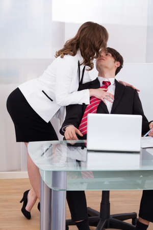 Sensuous secretary seducing businessman at desk in office photo