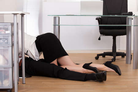 Low section of young business couple getting intimate on floor in office