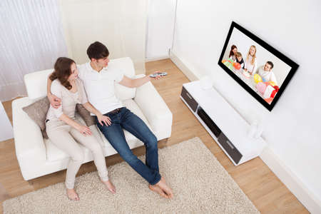 Young Couple In Livingroom Sitting On Couch Watching Television photo