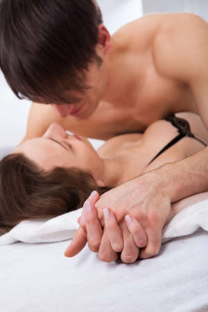 Lusty young couple having prelude in bed at home photo