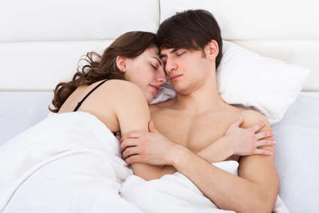 Loving young couple sleeping together in bed at home photo