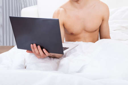 Midsection of shirtless man holding laptop in bed at home photo