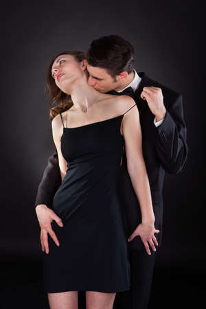 Young man in suit kissing woman on neck while removing dress strap from her shoulder isolated over black background photo