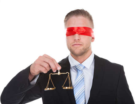 impartiality: Lawyer or judge with the scales of justice in his hand wearing a blindfold  conceptual of impartiality and fairness