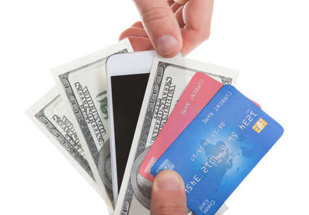 methods: Hand holding banknotes  credit cards and a tablet with a second hand selecting the tablet as a method of purchase and payment for merchandise  isolated on white