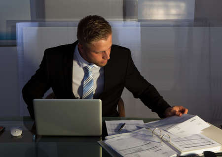 under pressure: Businessman under pressure working overtime late into the evening sitting at his desk collating a report for a deadline in the morning