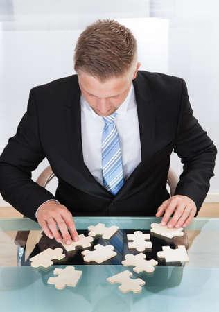 overcome a challenge: Businessman solving a jigsaw puzzle at his desk sitting down with the pieces spread out in front of him  conceptual of problem solving and challenges and work