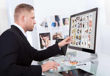 Zakenman zittend aan zijn bureau in de voorkant van een groot beeldscherm bewerken van foto's