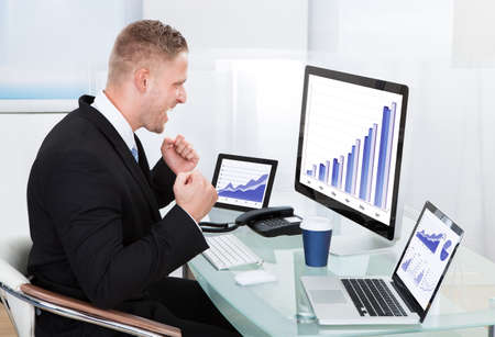 Businessman celebrating a performance graph sitting at his desk with statistical reports spread over three monitors cheering and clasping his fists photo