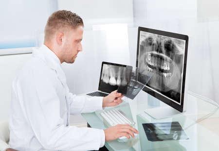 dentition: Medico o il radiologo guardando una radiografia in linea visualizzato su un monitor desktop come fa una diagnosi o prognosi controlli