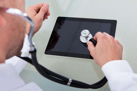 Doctor analyzing the health of tablet computer listening to the touchscreen with his stethoscope in a spoof conceptual image