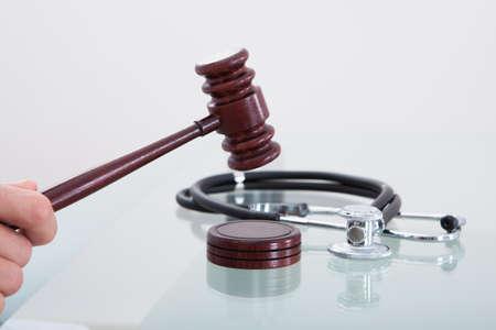 Jueces martillo y un estetoscopio en una imagen conceptual de una sentencia en una demanda por negligencia médica