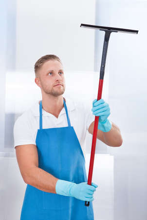 Male janitor using a squeegee to clean a window in an office wearing an apron and gloves as he works photo
