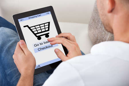 purchase icon: Conceptual image of a man making an online purchase on his tablet computer with a view of the screen showing a shopping cart and the text for checking out