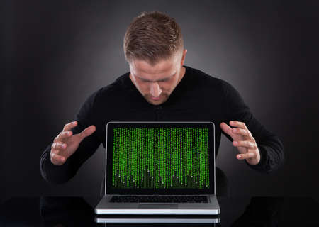 insecure: Man or hacker stealing data from a laptop at night bending forwards over the keyboard in the glow from the screen as he browses the internet or retrieves and downloads personal data Stock Photo