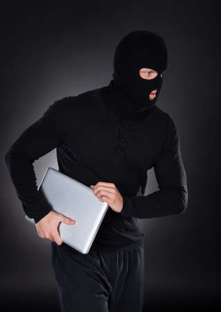 Thief stealing a laptop computer creeping furtively through the darkness as he makes his getaway  conceptual of data and identity theft photo