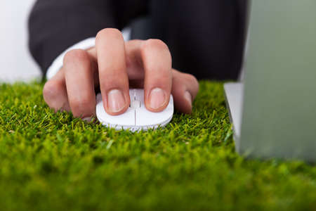 Midsection of businessman using laptop with computer mouse on grass photo