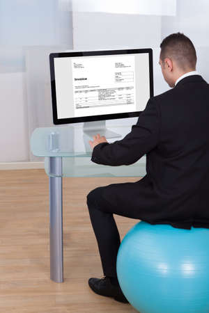 Rear view of businessman sitting on pilates ball and using computer in office photo