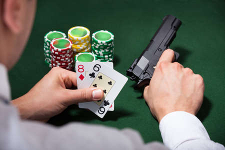 Rear view of man playing poker while holding gun in casino photo