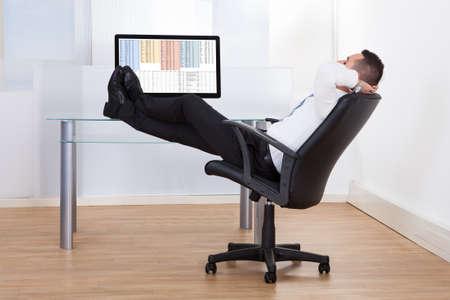 사무실 책상까지 편안한 젊은 사업가 앉아 다리의 측면보기