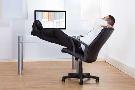 Side view of relaxed young businessman sitting feet up at office desk photo
