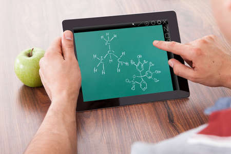 cropped image: Cropped image of young male student studying chemical formulas on digital tablet by green apple on table Stock Photo