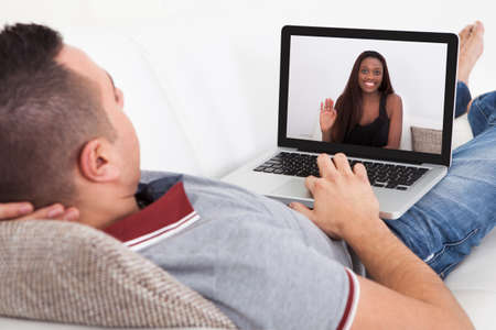 Young man having video chat with girlfriend on laptop at home photo