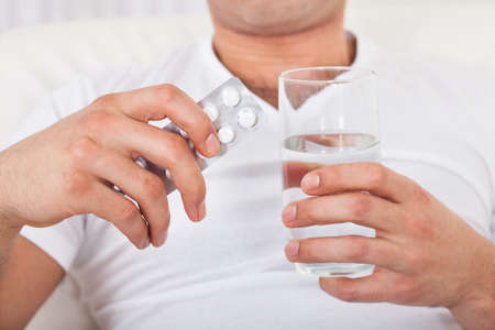 Young man with pack of pills and water glass at home photo