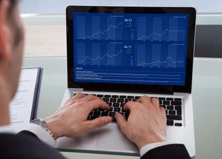 cropped: Cropped image of businessman using laptop at desk in office