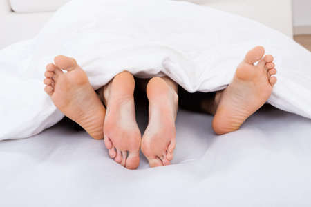 Low section of intimate couple under blanket on mattress at home