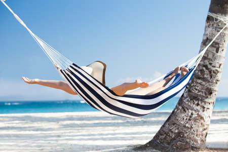 descansando: Mujer joven feliz que estira en hamaca en la playa