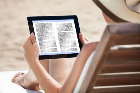 Woman reading eBook while relaxing on beach chair photo