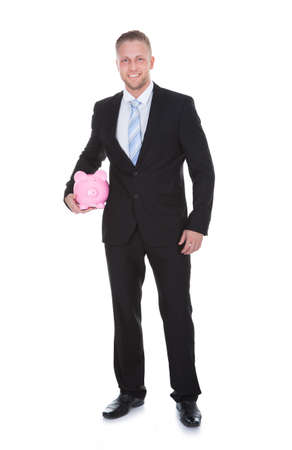 bank manager: Stylish businessman in a suit standing holding a pink ceramic piggy bank under his arm as he smiles at the camera in a conceptual financial  savings mad investment image  isolated on white Stock Photo