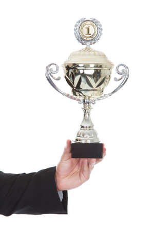 triumphant: Hand of a businessman displaying a large silver trophy cup as a reward for his success and achievement isolated on white