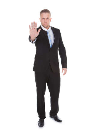 Handsome bearded businessman holding up his hand in a stop or halt gesture as he forbids entry or brings something to an end  isolated on white