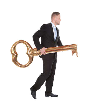 side keys: Businessman carrying an old-fashioned large brass key as he walks along conceptual of opportunity  achievement  ownership and security  isolated on white Stock Photo