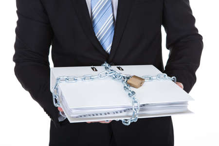 Businessman holding a top secret confidential file locked up with a chain and padlock to prevent unauthorized access  isolated on white photo