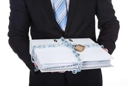 Zakenman die een top secret vertrouwelijk bestand opgesloten met een ketting en hangslot om onbevoegde toegang te voorkomen op wit wordt geïsoleerd Stockfoto