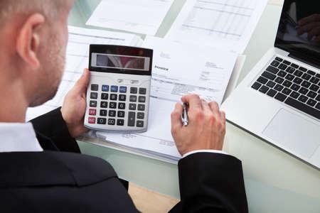 高角度の計算機および書類事務の上に見下ろすレポートの数字をチェックする実業家の肩越し