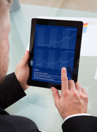over the shoulder view: Businessman navigating on his tablet-pc using his finger on the touchscreen as he studies an online report  over the shoulder view of the screen Stock Photo