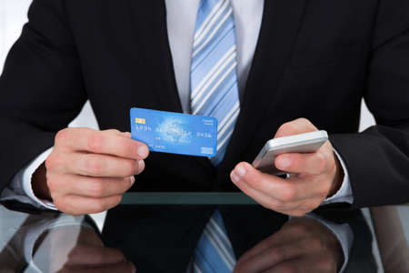 dank: Businessman doing online banking or making a purchase through an online store using his dank credit card  and a mobile phone close up view of his hands