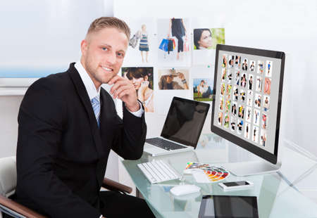 Businessman sitting at his desk in front of a large screen monitor editing photographs Imagens