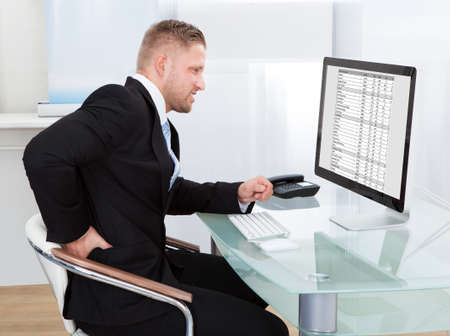 Businessman rubbing his back as he sits working at his desk in font of his large desktop monitor as he eases the stiffness photo