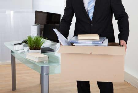 すべての彼の個人的な持ち物と茶色の段ボール箱にファイルを荷造りオフィスの移動のビジネスマン