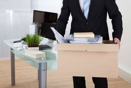 resignation: Businessman moving offices packing up all his personal belongings and files into a brown cardboard box