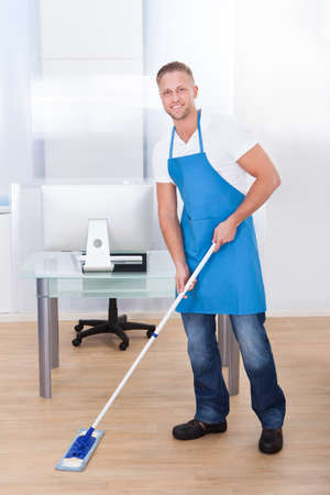desinfectante: Conserje masculino hermoso o un limpiador de la limpieza del piso en un edificio de oficinas utilizando una fregona para lavar y desinfectar la superficie de la
